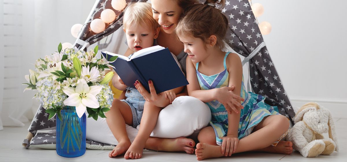 Child reading book with another child and mom watching.
