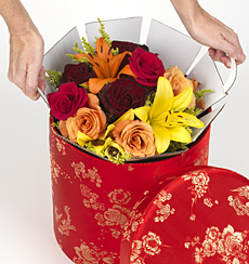 "During transit, the bouquet is held securely in place by a ""flower girl"", a cardboard insert that protects the blooms and keeps the bouquet in perfect position inside the hatbox."